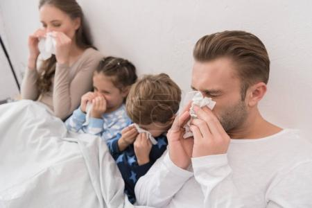 Photo pour Parents malades avec fils et fille couchés dans un lit et le nez soufflant dans des serviettes - image libre de droit