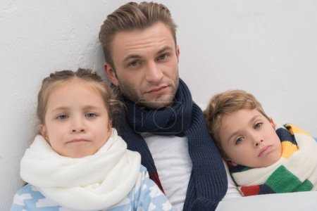 Sick father with son and daughter in bed