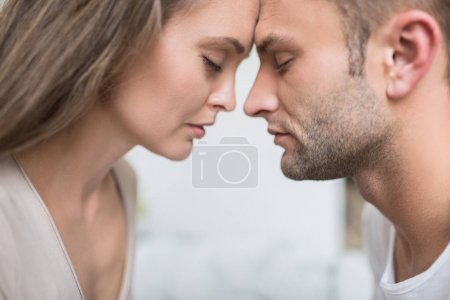 Photo for Young attractive couple touching foreheads with eyes closed - Royalty Free Image