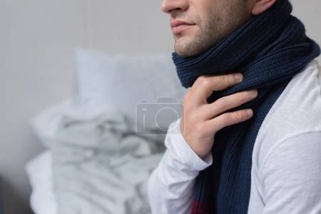 sick man with scarf over neck