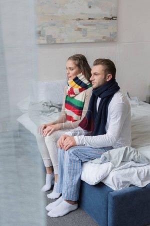 Sick couple with scarfs over necks