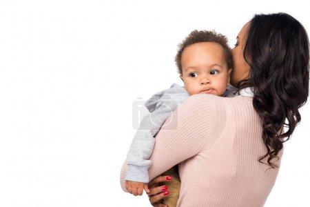 Photo pour Vue arrière du mère afro-américaine transportant adorable petit enfant isolé sur blanc - image libre de droit