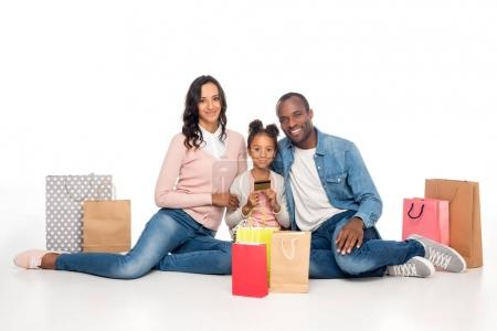 Photo pour Heureuse famille afro-américaine avec des sacs à provisions et carte de crédit souriant à la caméra isolée sur blanc - image libre de droit