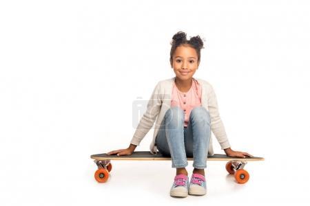Photo pour Adorable enfant afro-américain assis sur planche à roulettes et souriant à la caméra isolé sur blanc - image libre de droit