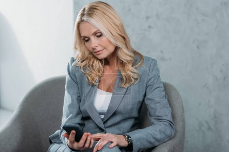 Photo for Thoughtful mature businesswoman using smartphone while sitting in armchair - Royalty Free Image