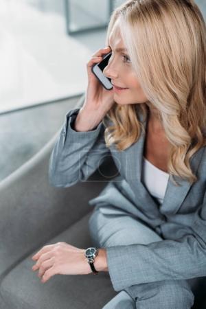Photo pour Vue grand angle de femme d'affaires parler par téléphone dans le fauteuil - image libre de droit