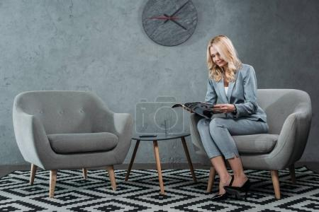 Photo for Businesswoman reading magazine while sitting in armchair at office lobby - Royalty Free Image