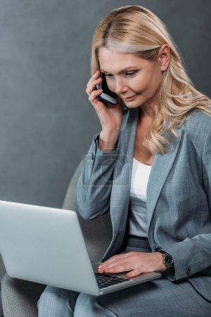 Foto de Atractiva madura empresaria hablando por teléfono durante el uso del ordenador portátil - Imagen libre de derechos