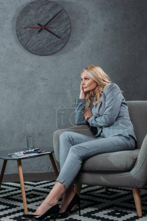 Photo pour Femme d'affaires mature réfléchie assise dans un fauteuil dans le hall du bureau - image libre de droit
