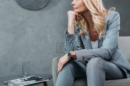 Photo pour Plan recadré d'une femme d'affaires réfléchie assise dans un fauteuil dans le hall du bureau - image libre de droit