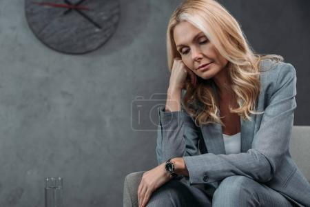 Photo pour Somnolent mature femme d'affaires assis dans le fauteuil - image libre de droit