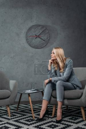 Photo pour Femme d'affaires mature pensif assis sur le fauteuil dans la salle d'attente au bureau moderne - image libre de droit