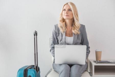 Photo pour Femme d'affaires mature réfléchie travaillant avec un ordinateur portable en attendant le voyage - image libre de droit