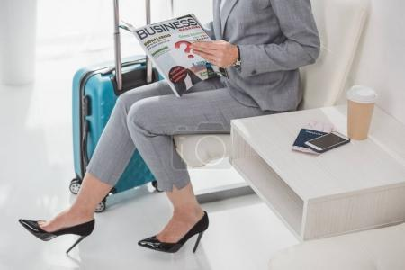 Photo for Cropped shot of mature businesswoman with magazine waiting for trip - Royalty Free Image