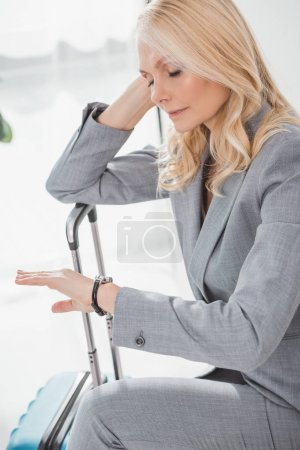 Photo for Exhausted mature businesswoman looking at watch while waiting for trip - Royalty Free Image