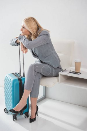 Photo for Tired mature businesswoman leaning on suitcase while waiting for trip - Royalty Free Image