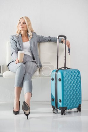 Photo for Thoughtful mature businesswoman with coffee to go waiting for trip - Royalty Free Image
