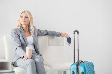 Photo pour Femme d'affaires réfléchie avec café pour aller attendre pour voyage - image libre de droit