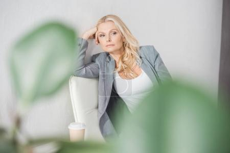 businesswoman with coffee in waiting room