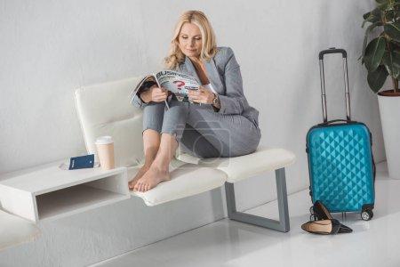 Photo pour Nu-pieds femme mature lire magazine pendant que vous attendez de voyage - image libre de droit