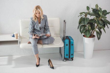 Foto de Empresaria madura atractiva lectura revista mientras espera para viaje - Imagen libre de derechos