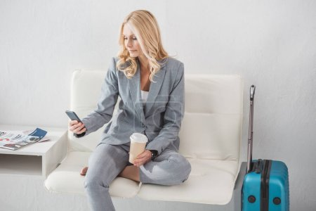 Photo for Beautiful mature businesswoman with coffee and smartphone waiting for trip - Royalty Free Image