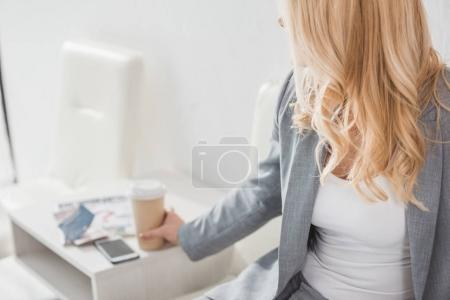 businesswoman taking paper cup of coffee