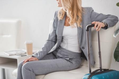 Photo pour Plan recadré de femme d'affaires avec des bagages et du café pour aller attendre le voyage - image libre de droit