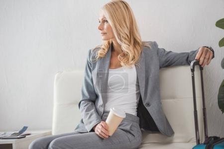 Photo pour Femme d'affaires avec café pour aller s'asseoir sur une chaise avec valise et regarder ailleurs - image libre de droit