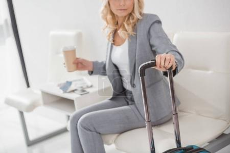 businesswoman with suitcase and coffee to go