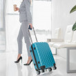 Cropped shot of businesswoman with luggage and cof...