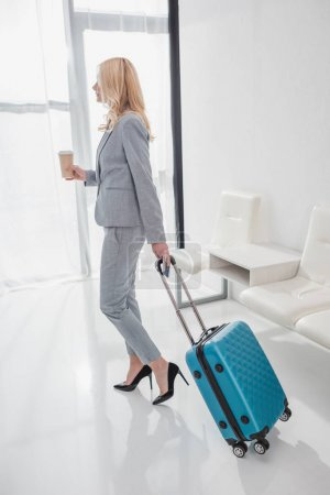 businesswoman with luggage and coffee to go