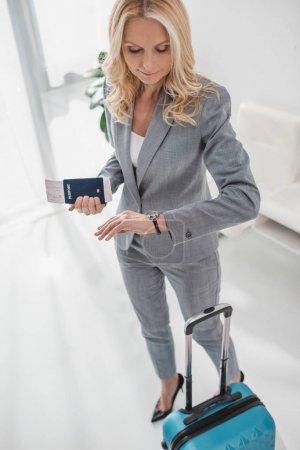 Photo pour Vue d'angle élevé de femme d'affaires avec valise regardant montre tout en attente vol - image libre de droit