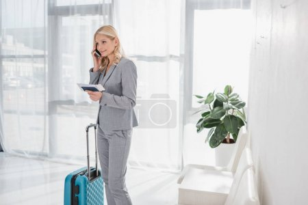 businesswoman ready for flight talkign by phone