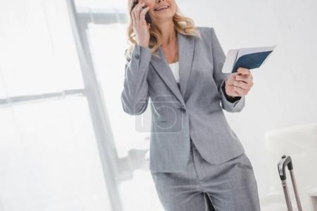 businesswoman with flight ticket talking by phone