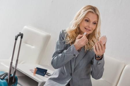Photo pour Heureux mature femme d'affaires faisant maquillage avant le voyage - image libre de droit