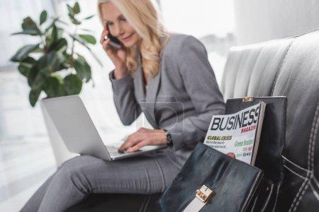 Photo pour Magazine d'affaires en sac avec femme d'affaires floue parlant par téléphone sur fond - image libre de droit