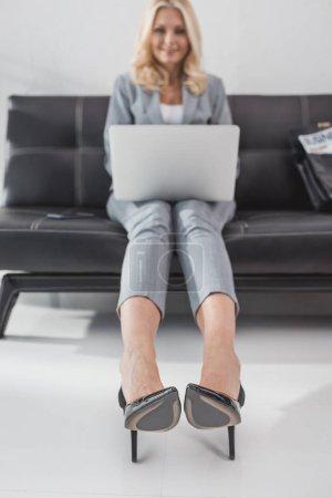 Photo pour Femme d'affaires élégant travaillant avec ordinateur portable sur le canapé - image libre de droit