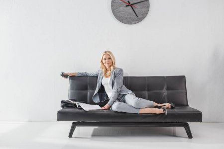 Photo for Stylish mature businesswoman relaxing on couch with magazine - Royalty Free Image