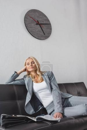 businesswoman relaxing on couch with magazine