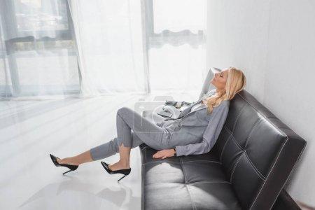 Photo pour Détente femme mature assise sur le canapé dans le hall de l'hôtel - image libre de droit