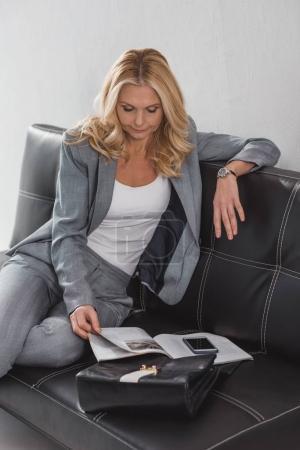 Photo pour Magazine de lecture femme d'affaires tout en se relaxant sur le canapé - image libre de droit