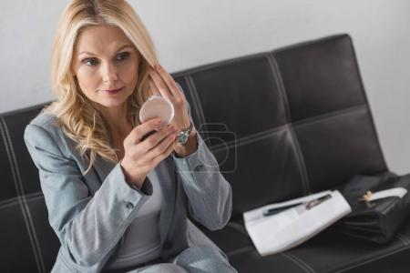 businesswoman looking at cosmetic mirror