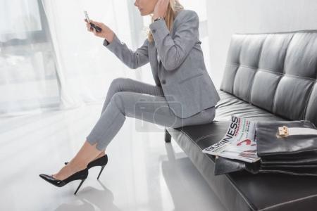 Foto de Mujer de negocios mirando al espejo cosmético mientras está sentada en el sofá en la sala de espera - Imagen libre de derechos
