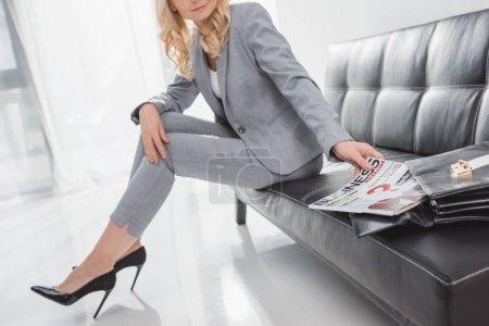 Photo pour Élégant femme d'affaires mature prenant magazine de sac tout en étant assis sur le canapé - image libre de droit
