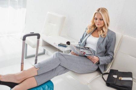 Photo pour Belle femme mature lire magazine pendant que vous attendez de voyage - image libre de droit