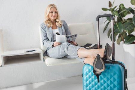 Photo pour Attrayante femme mature lire magazine pendant que vous attendez de voyage - image libre de droit