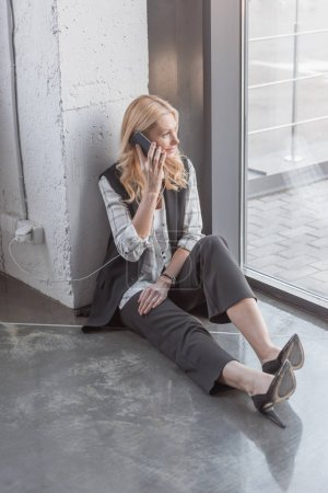 businesswoman charging smartphone and making call