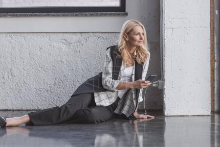 businesswoman charging smartphone