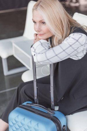 woman with luggage waiting for trip